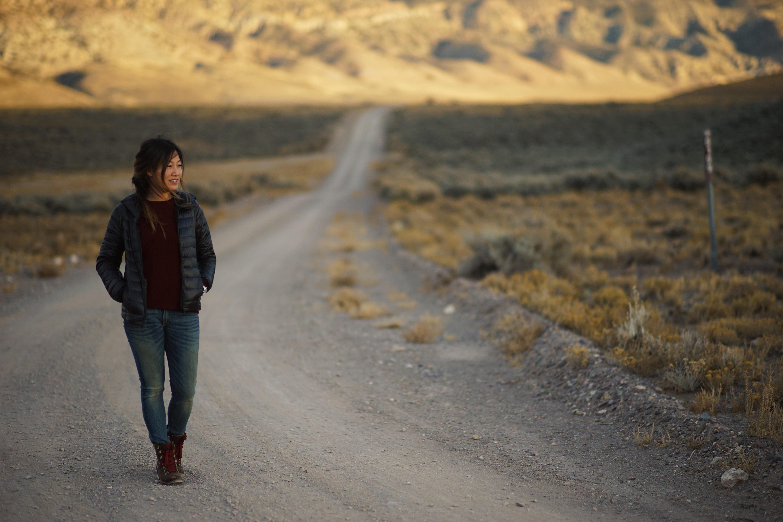 man walking on gray soil road