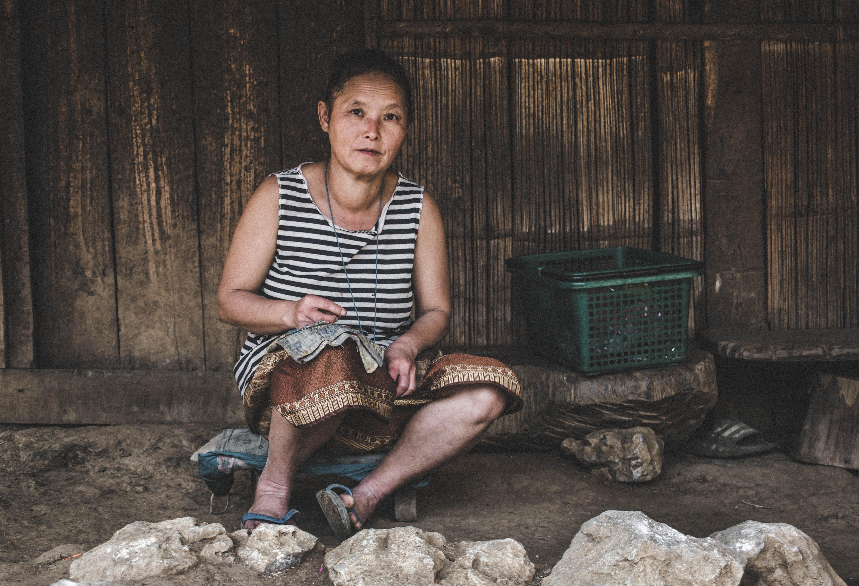 woman sitting near green plastic basket outside