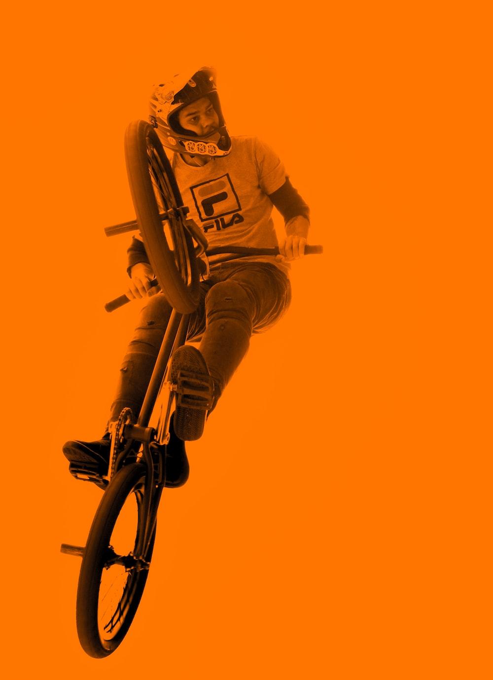 man riding BMX bicycle while doing tricks