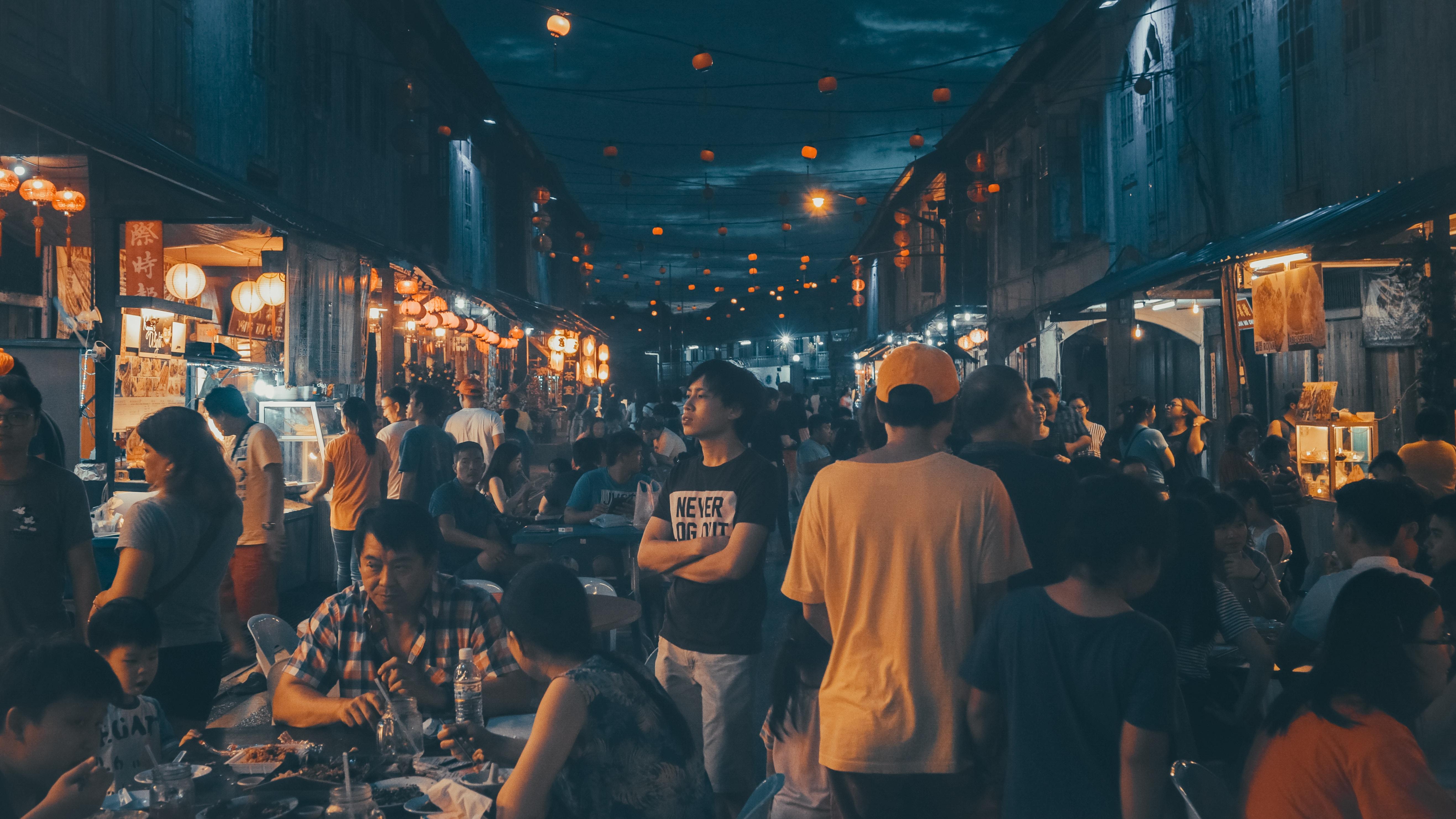 people gathering near street food stalls