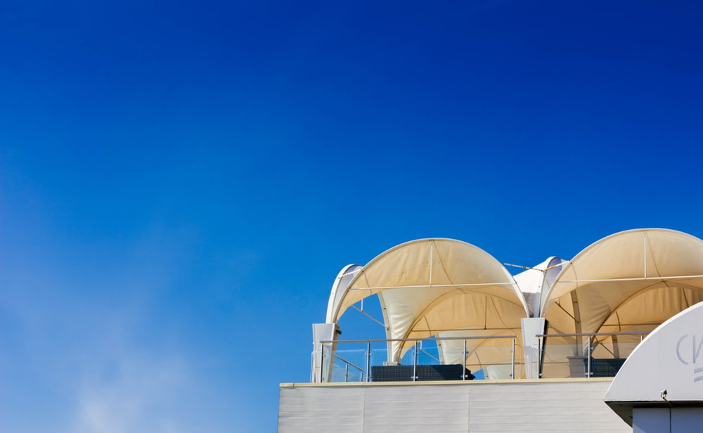 two brown tents on top of building under blue sky