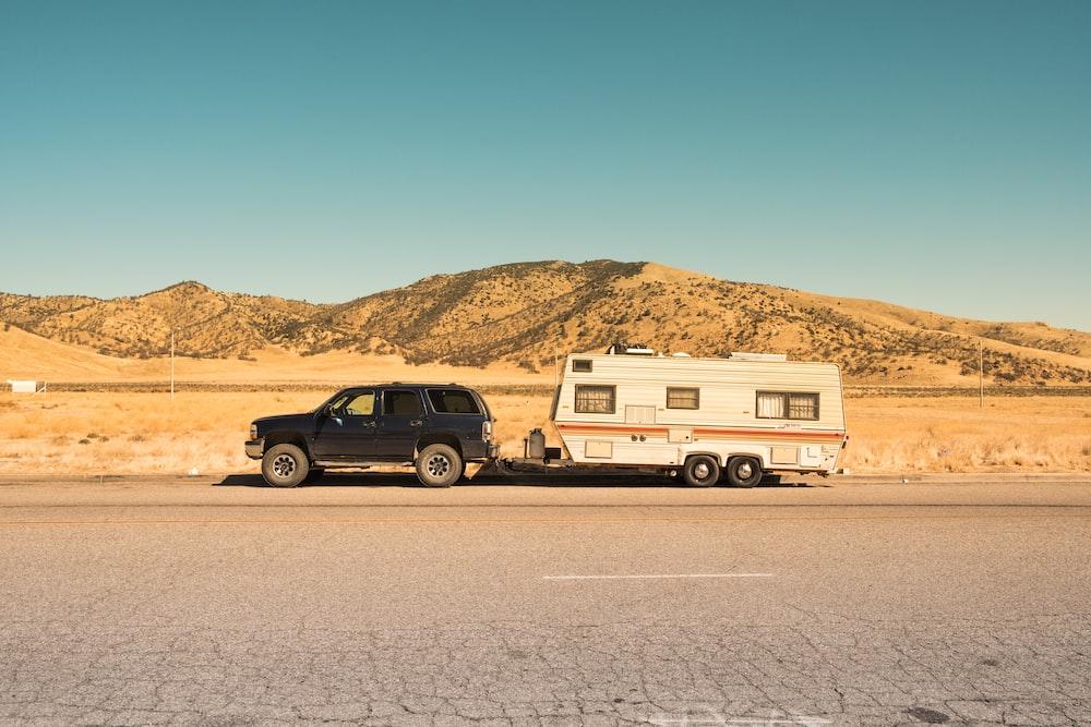 black SUV and white trailer