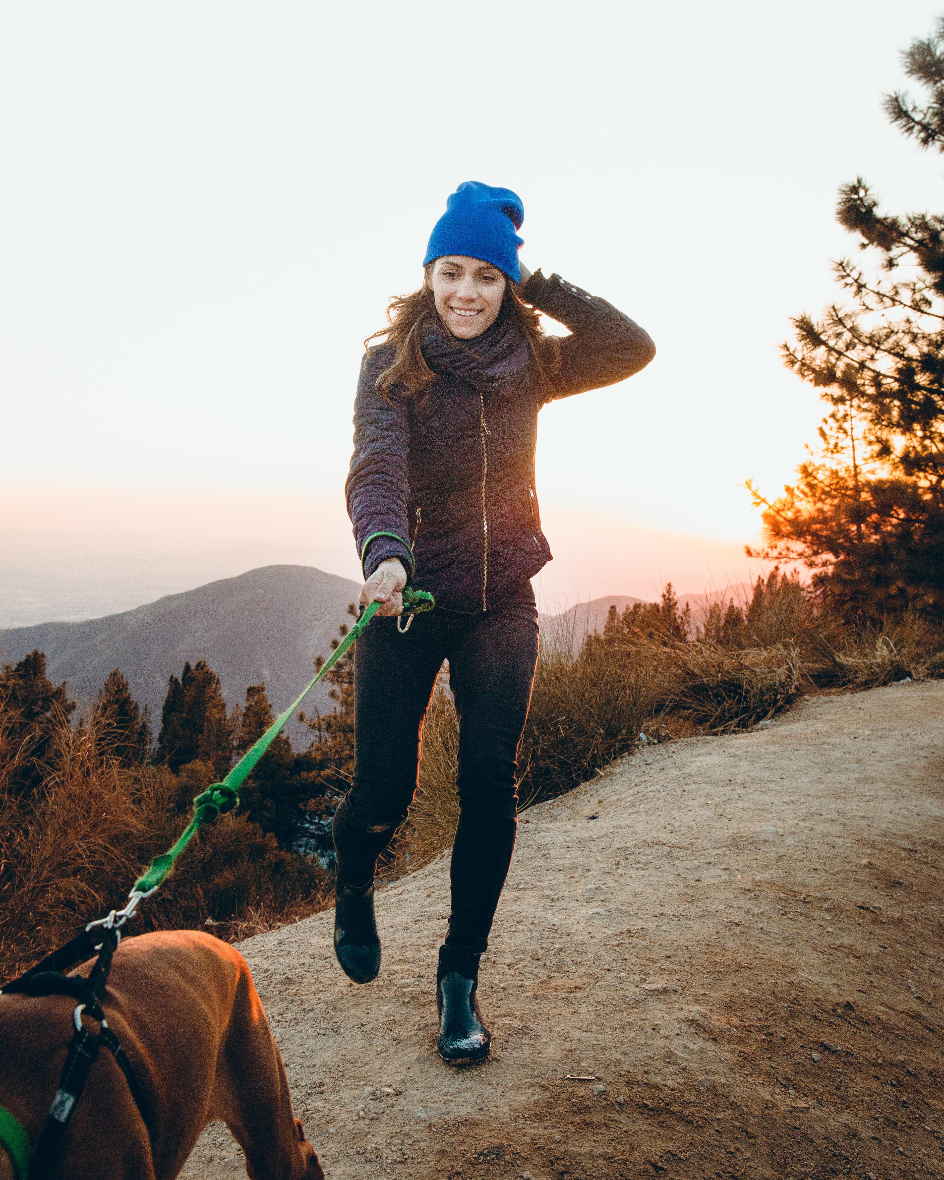woman holding green dog leash