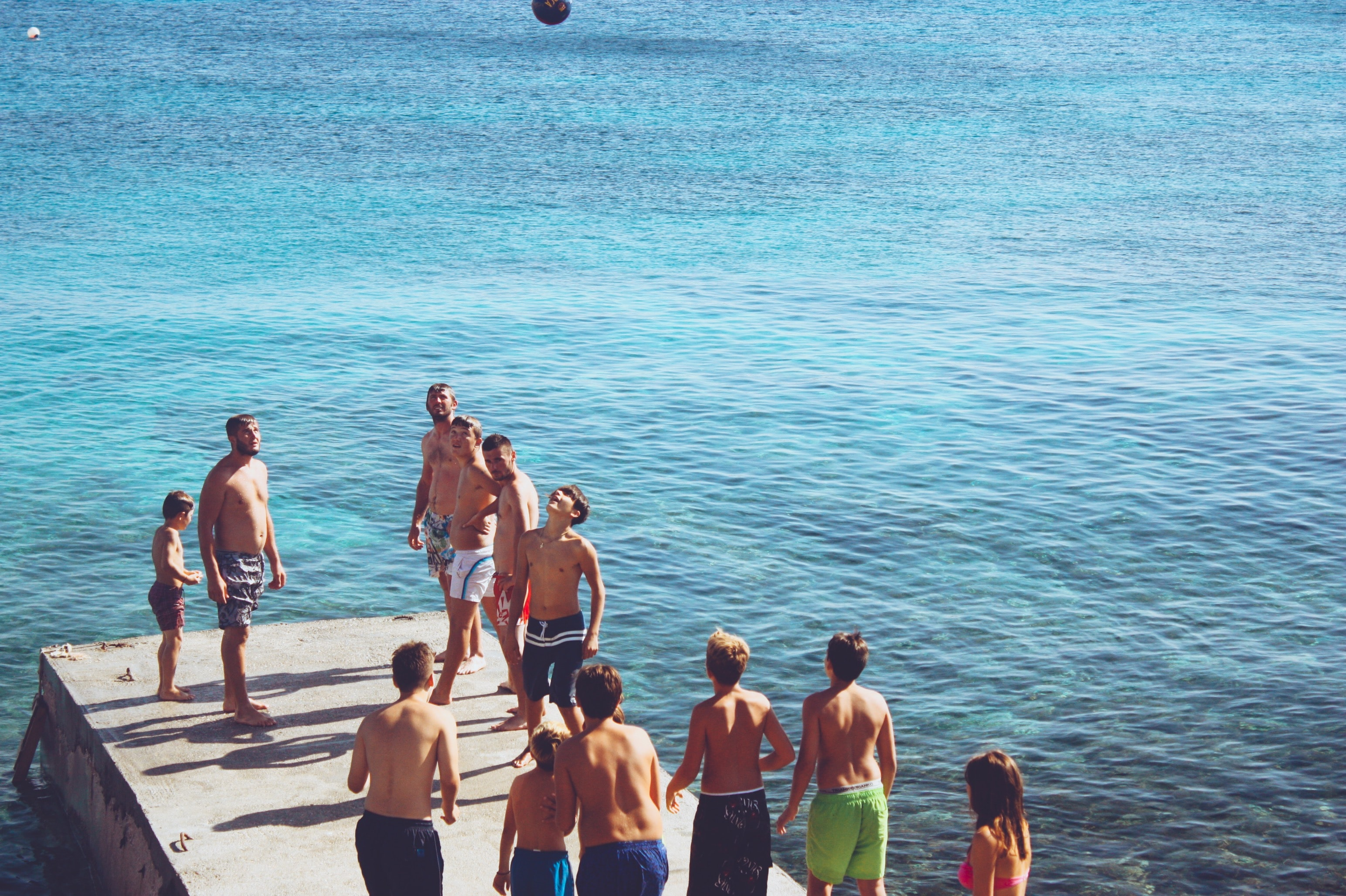 group of people playing ball on wooden dock