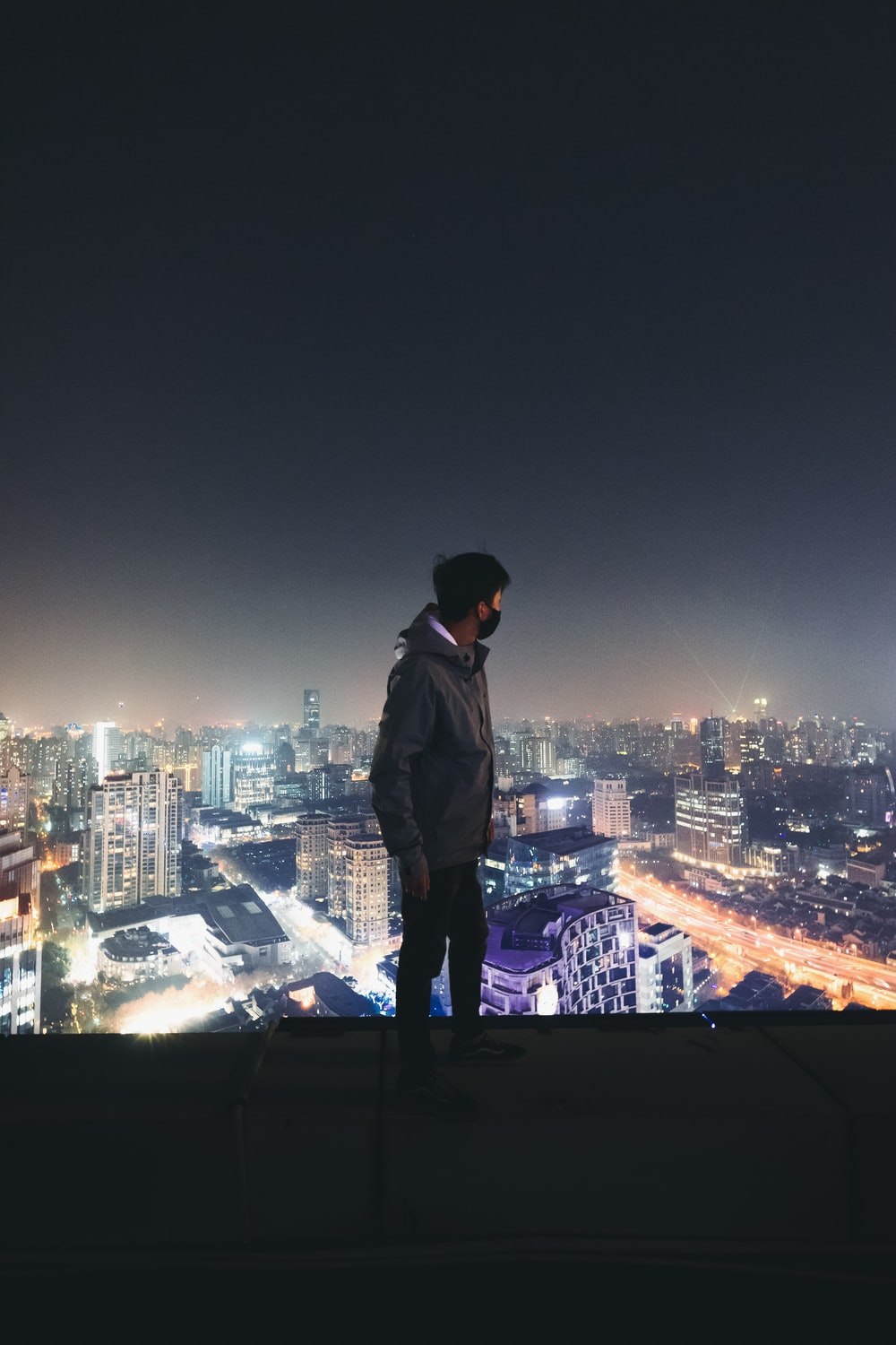 man in gray jacket watching high-rise buildings