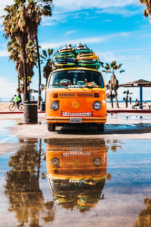 orange van with surfboard on top