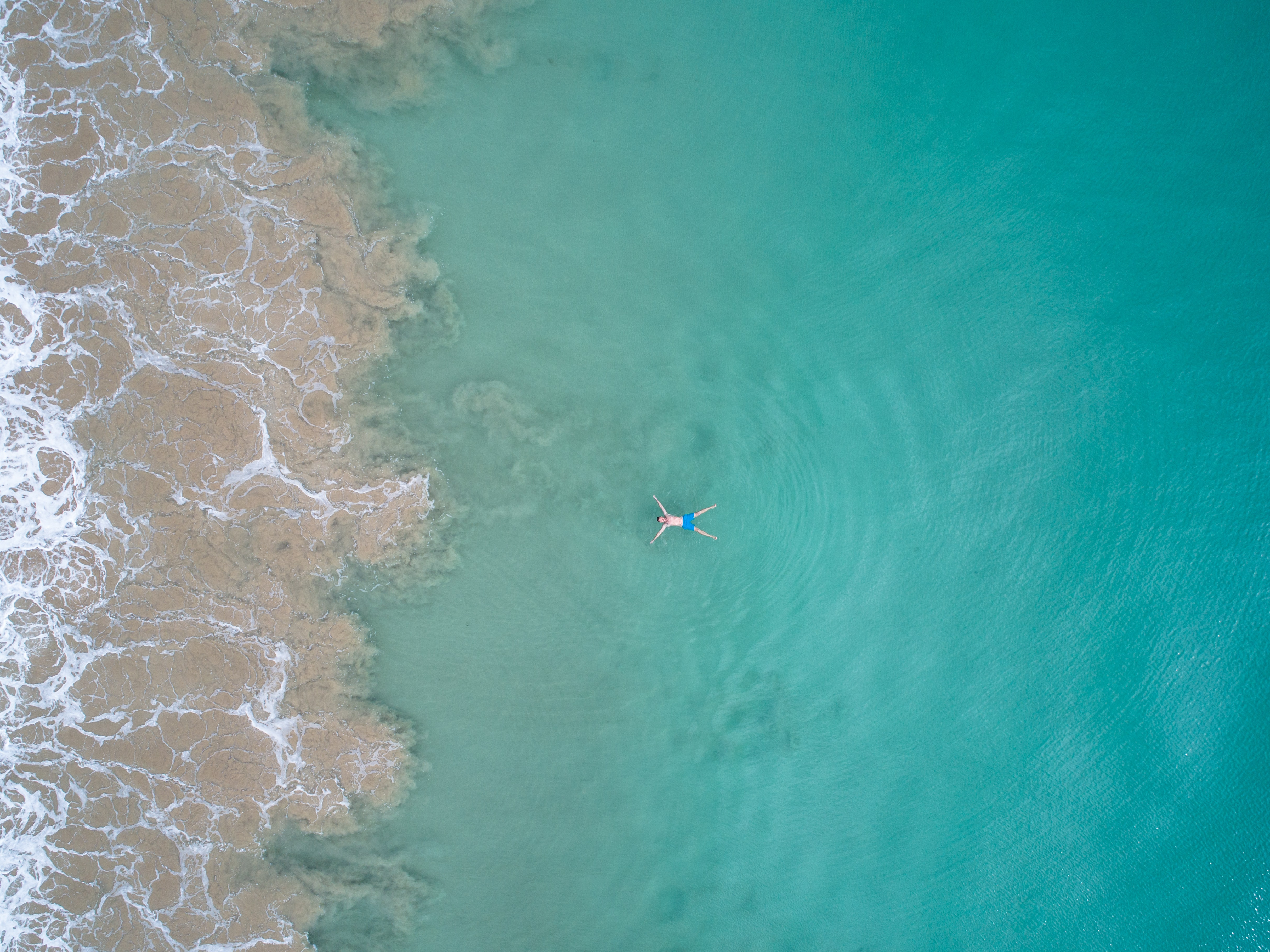 top view of person floating on beach