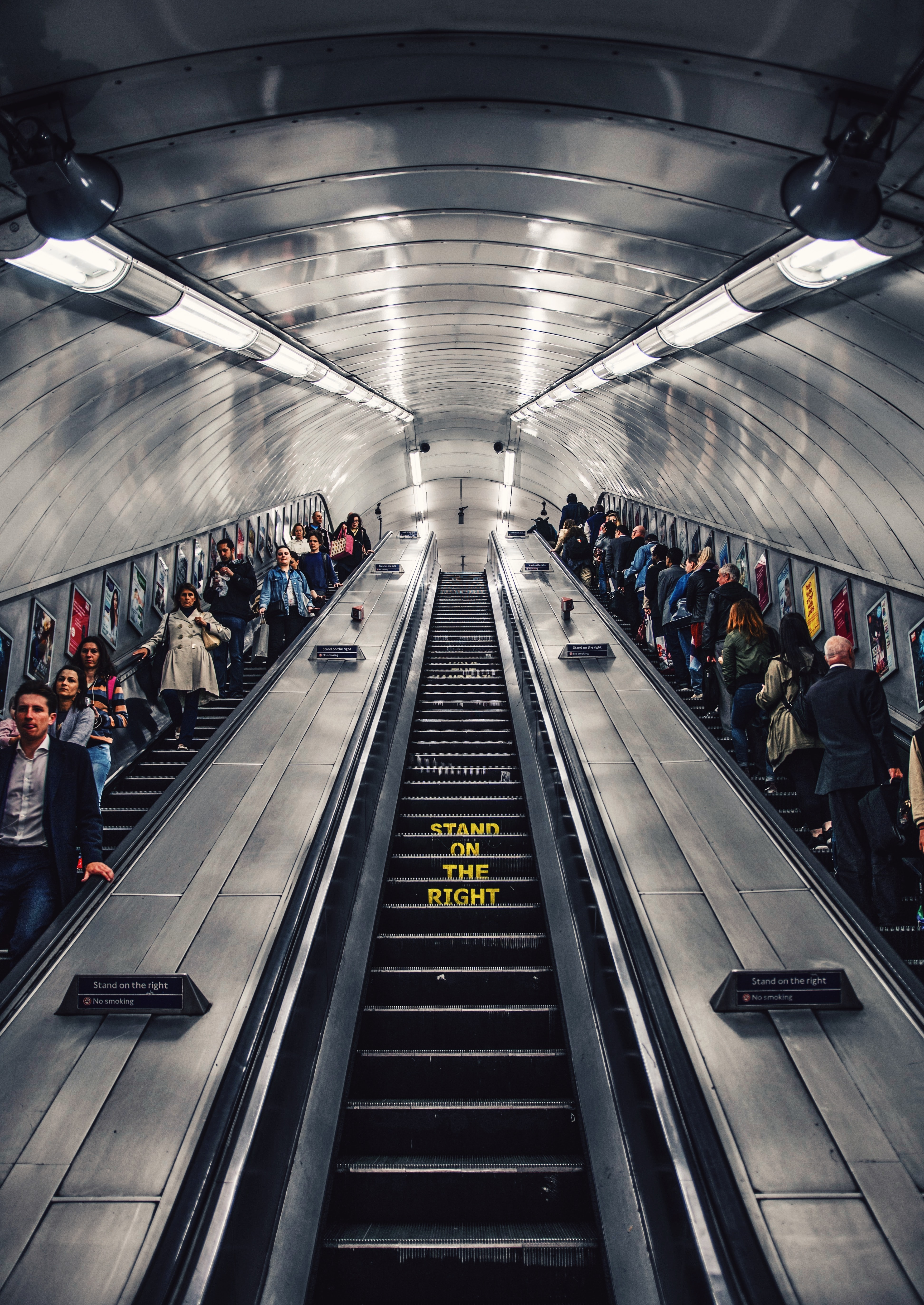people riding escalator