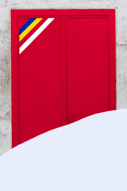 red wooden door on brown concrete wall