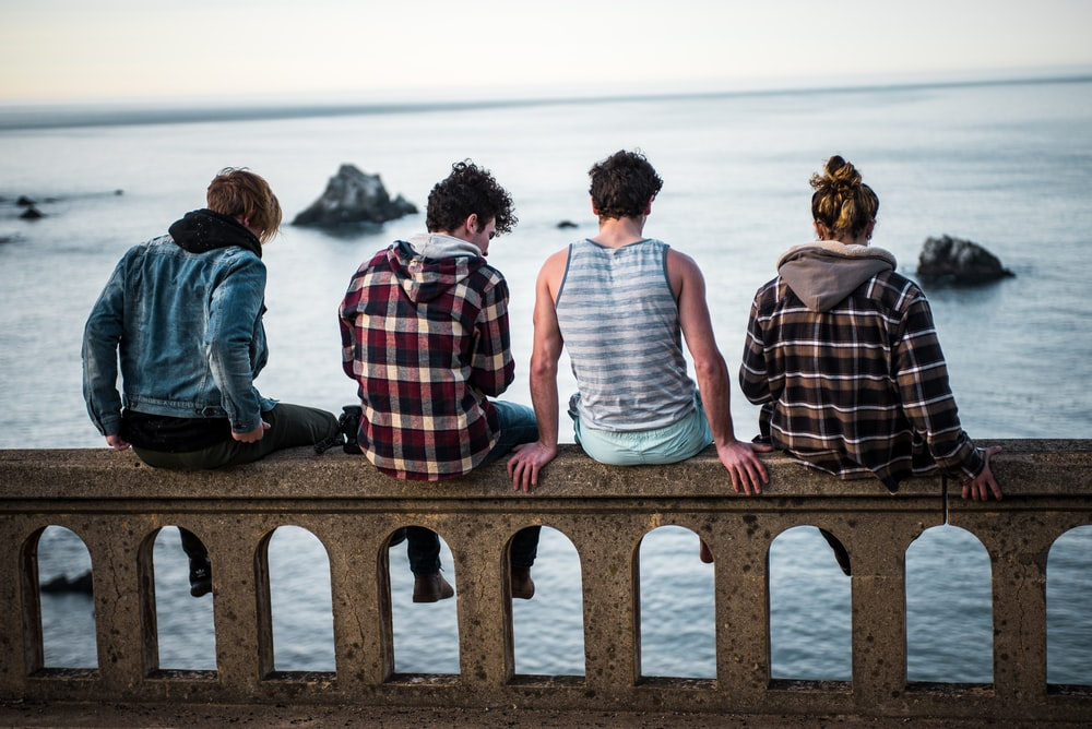 four person sitting on bench in front of body of water