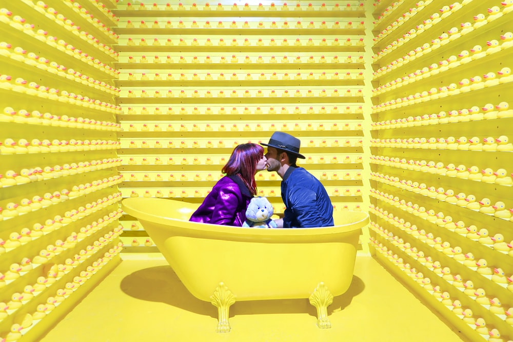 man and woman kissing inside yellow bathtub