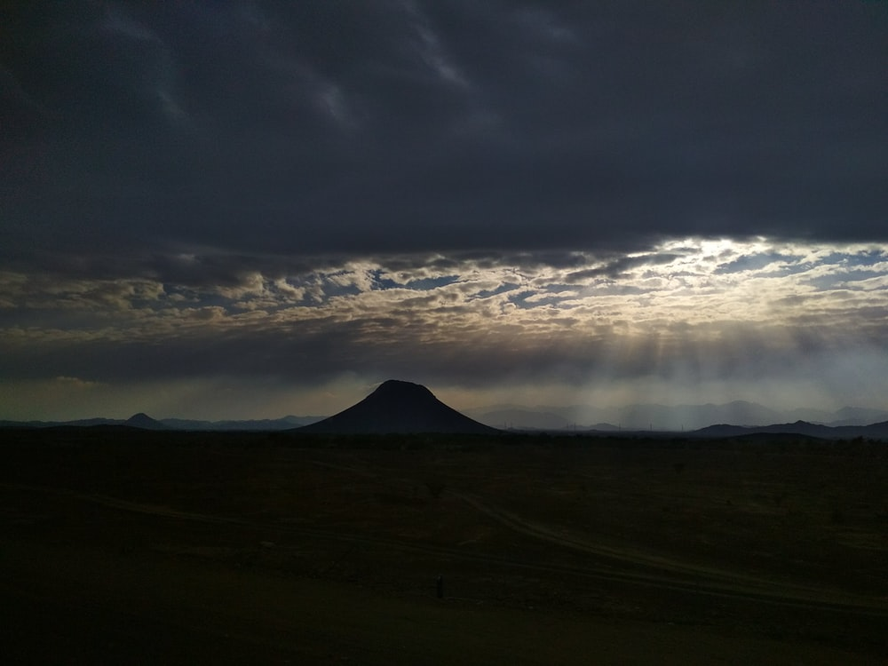 bird's eye view of mountain under cloudy sky with crepuscular rays