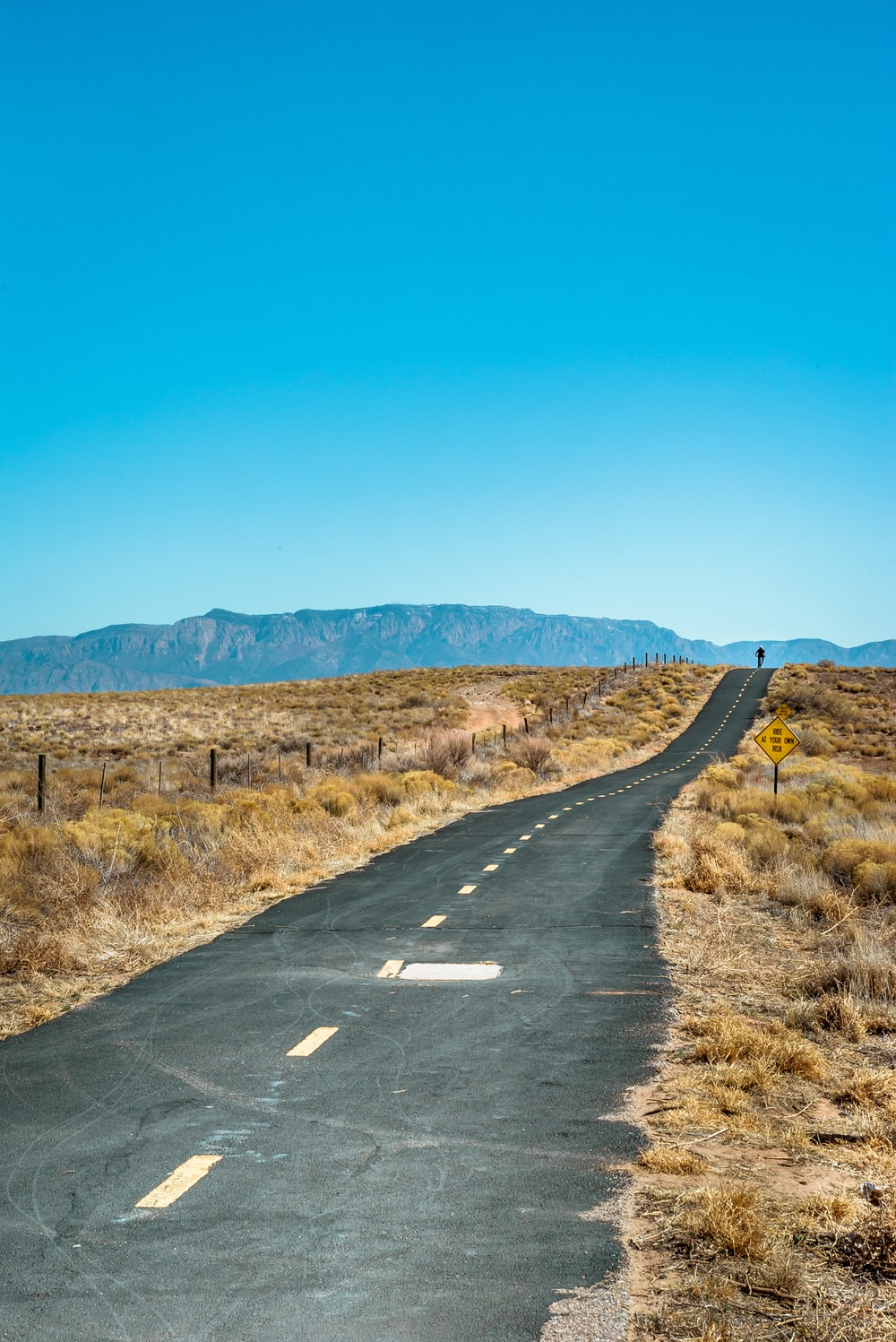 road with brown grass under blue skies