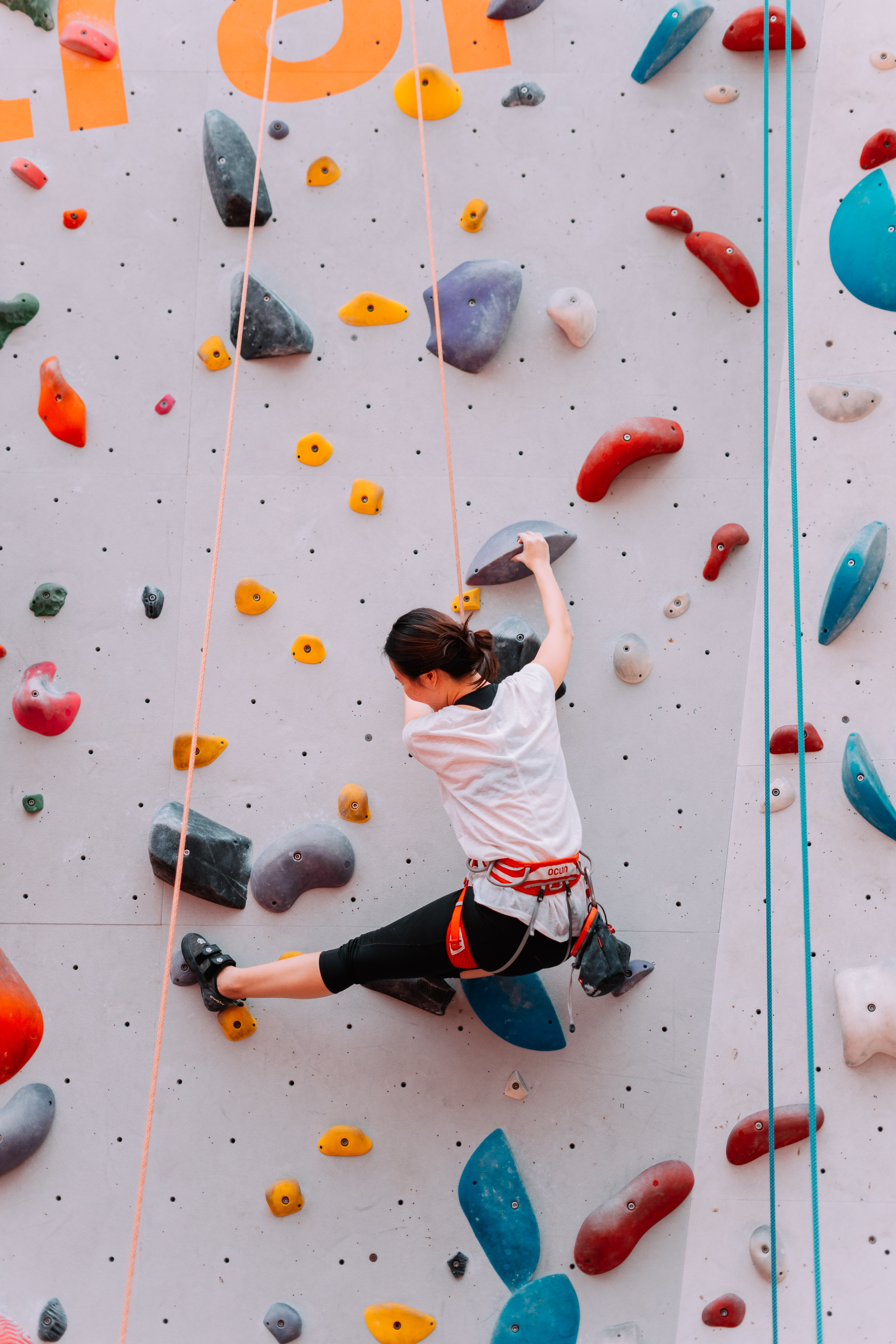 woman climbing on wall during daytime
