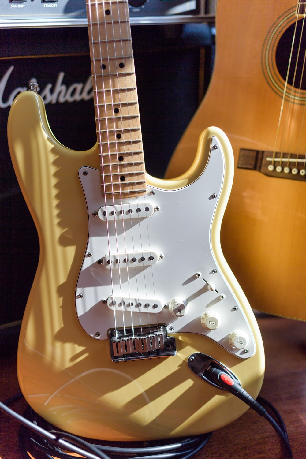 brown and white electric guitar