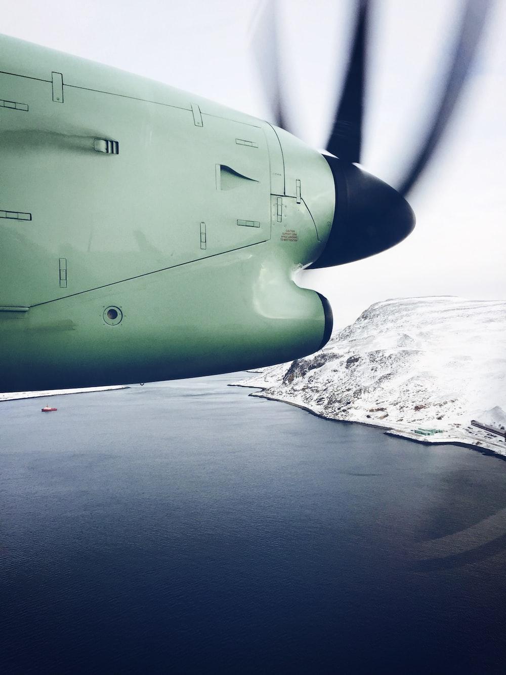 white plane flying over lake