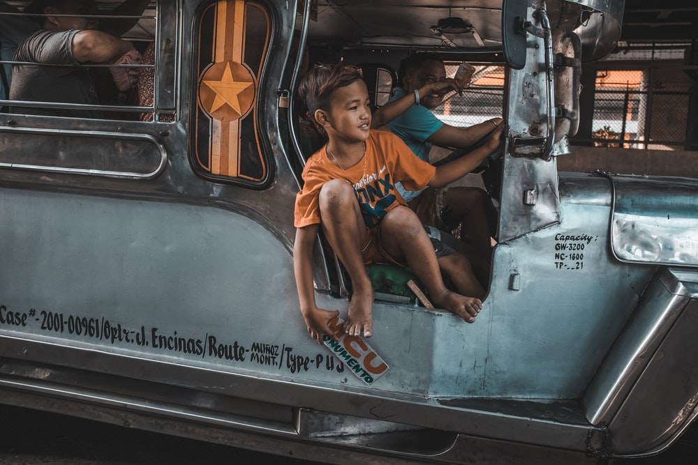 boy riding on jeepney with driver beside