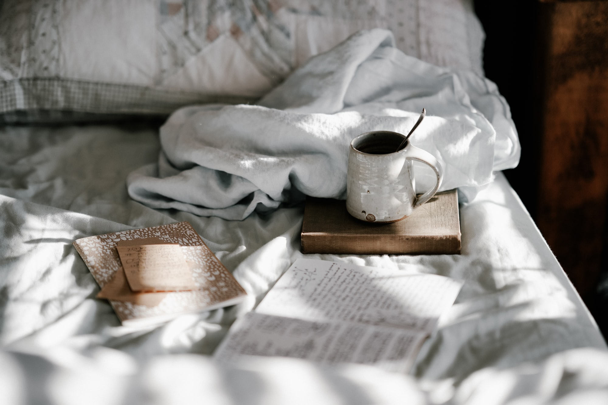 Mug and notebooks on bed