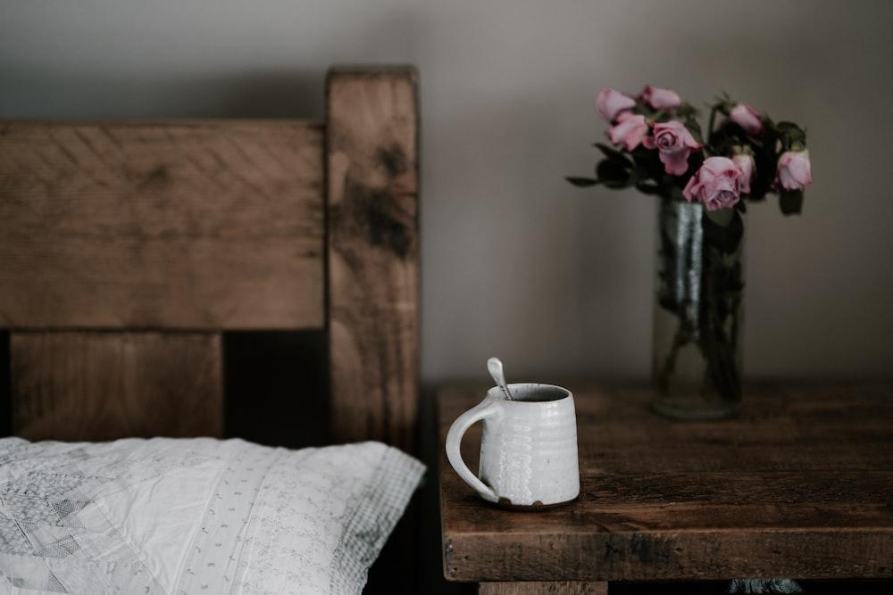 茶色の木製テーブルに白いマグカップ