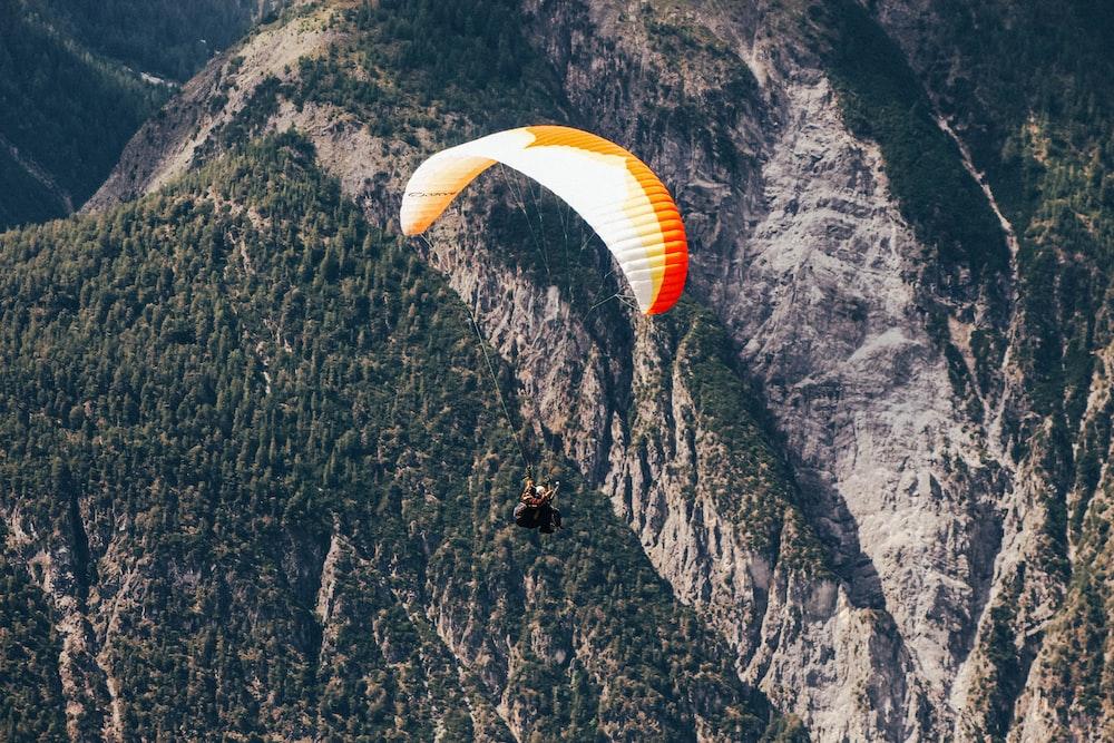bird's eye view photography of man parachuting near mountain