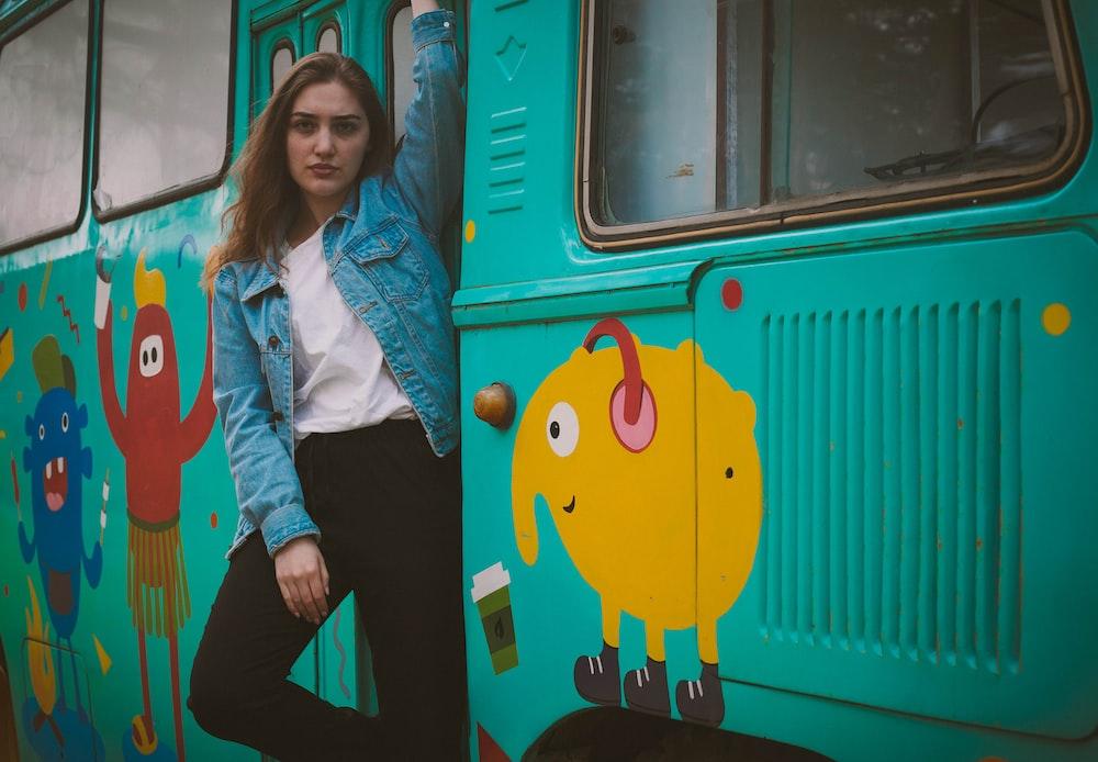 woman standing beside teal bus