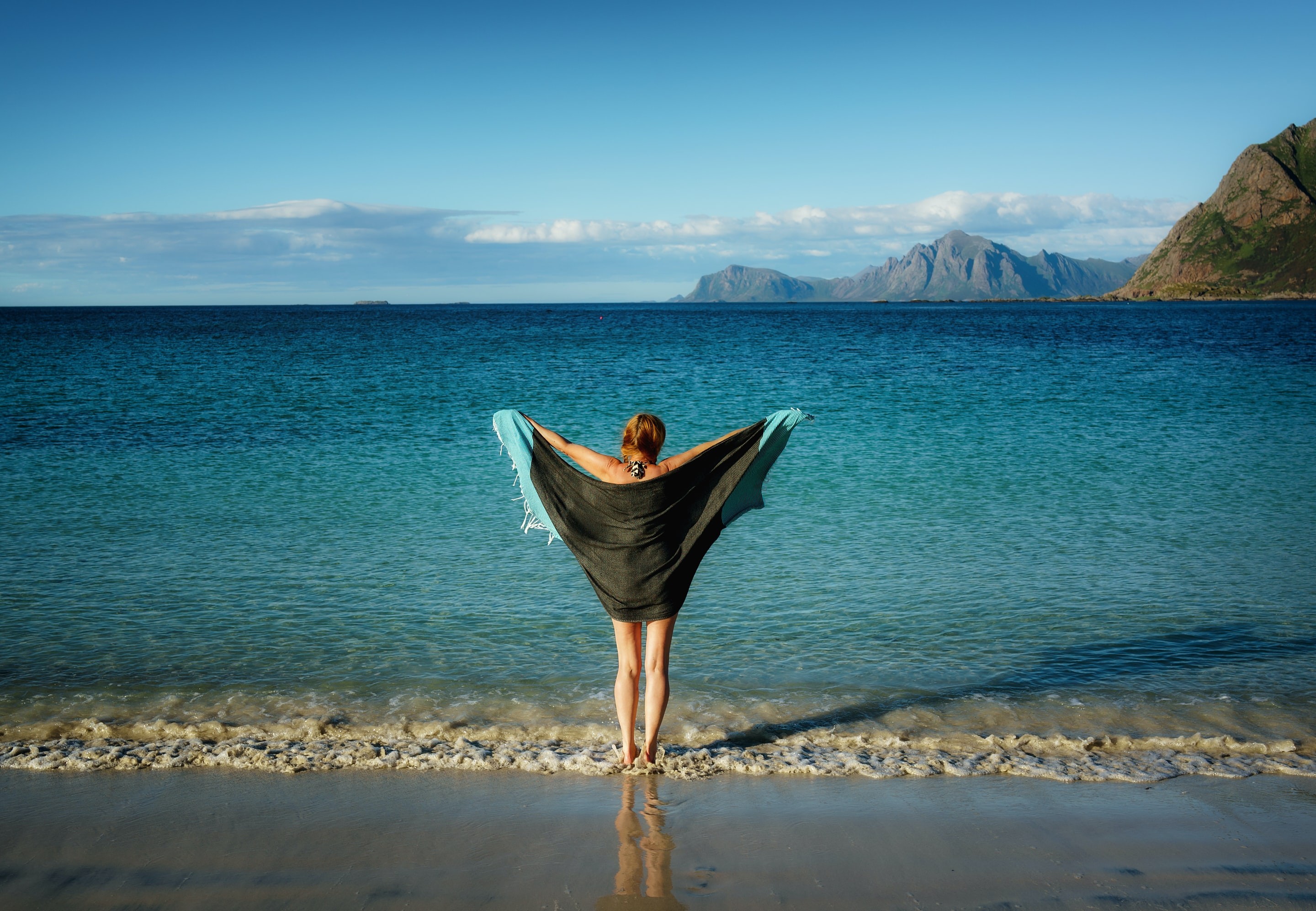 woman holding black towel standing on beach