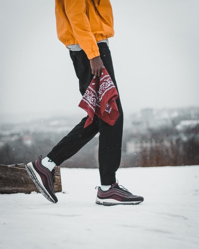 man walking on snow holding red and white paisley handkerchief near brown log during daytime