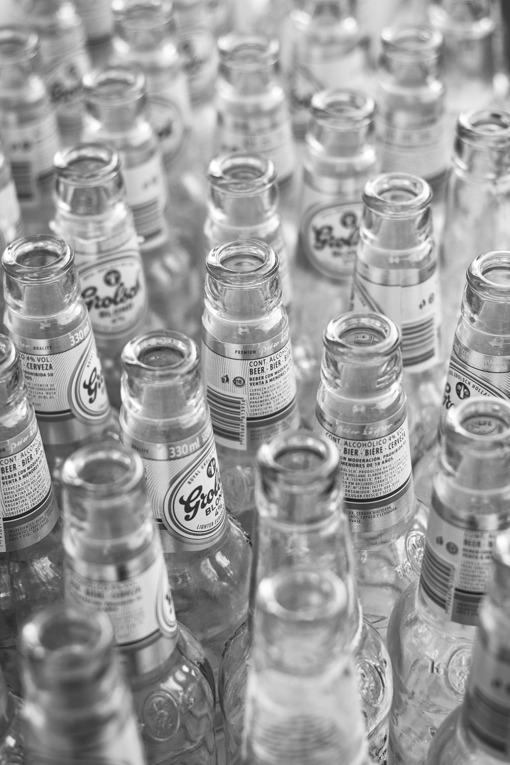 grayscale photo of glass bottles