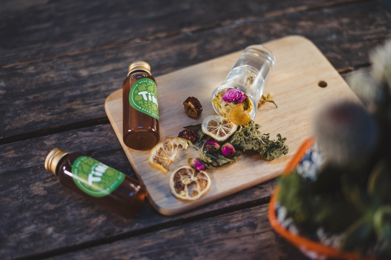 sliced lemon on chopping board along with brown glass bottles
