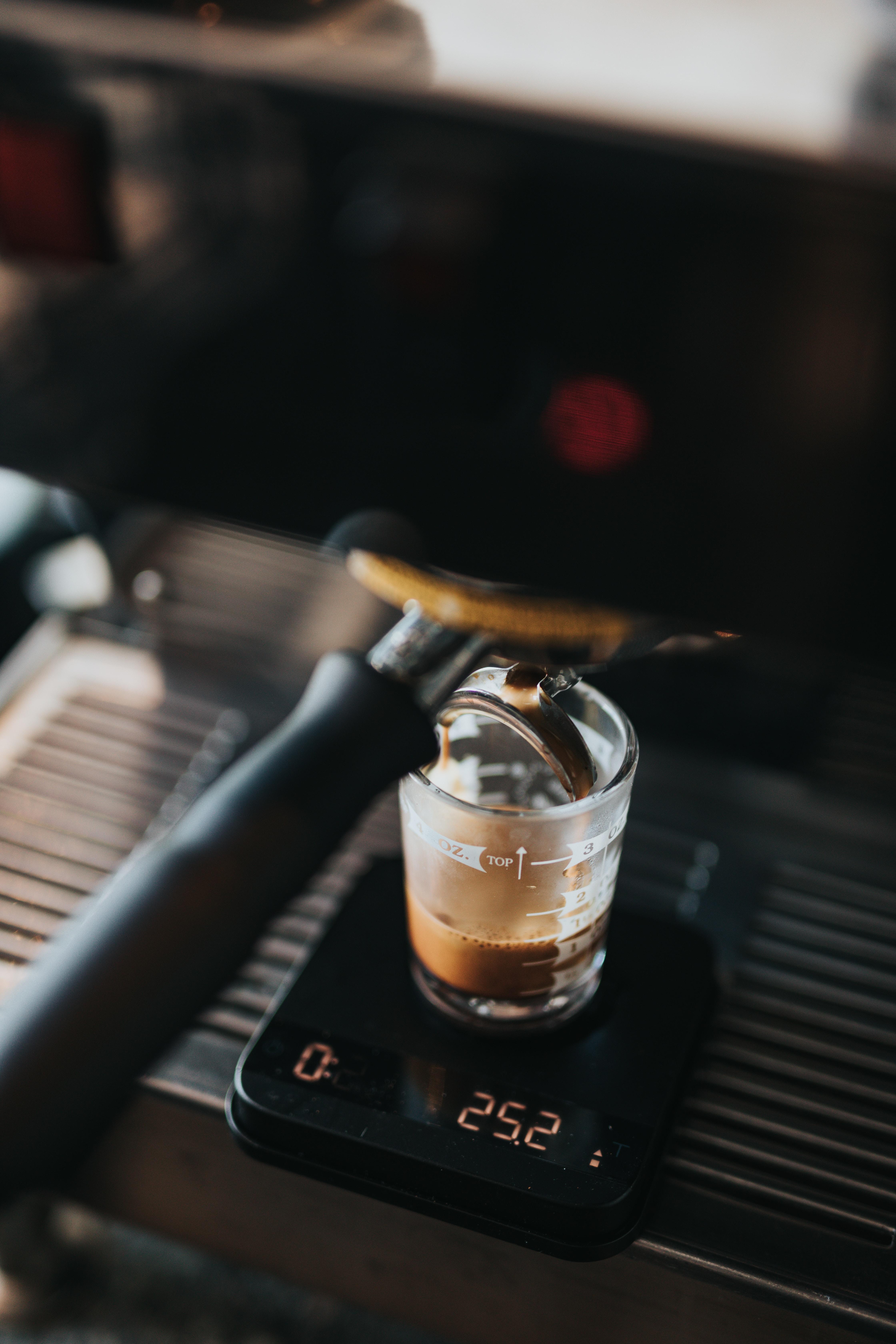 closeup photo of black espresso maker filing clear glass cup