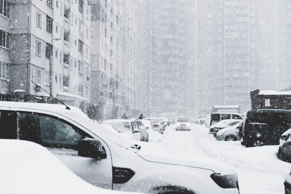 vehicles parked along the road covered with snow