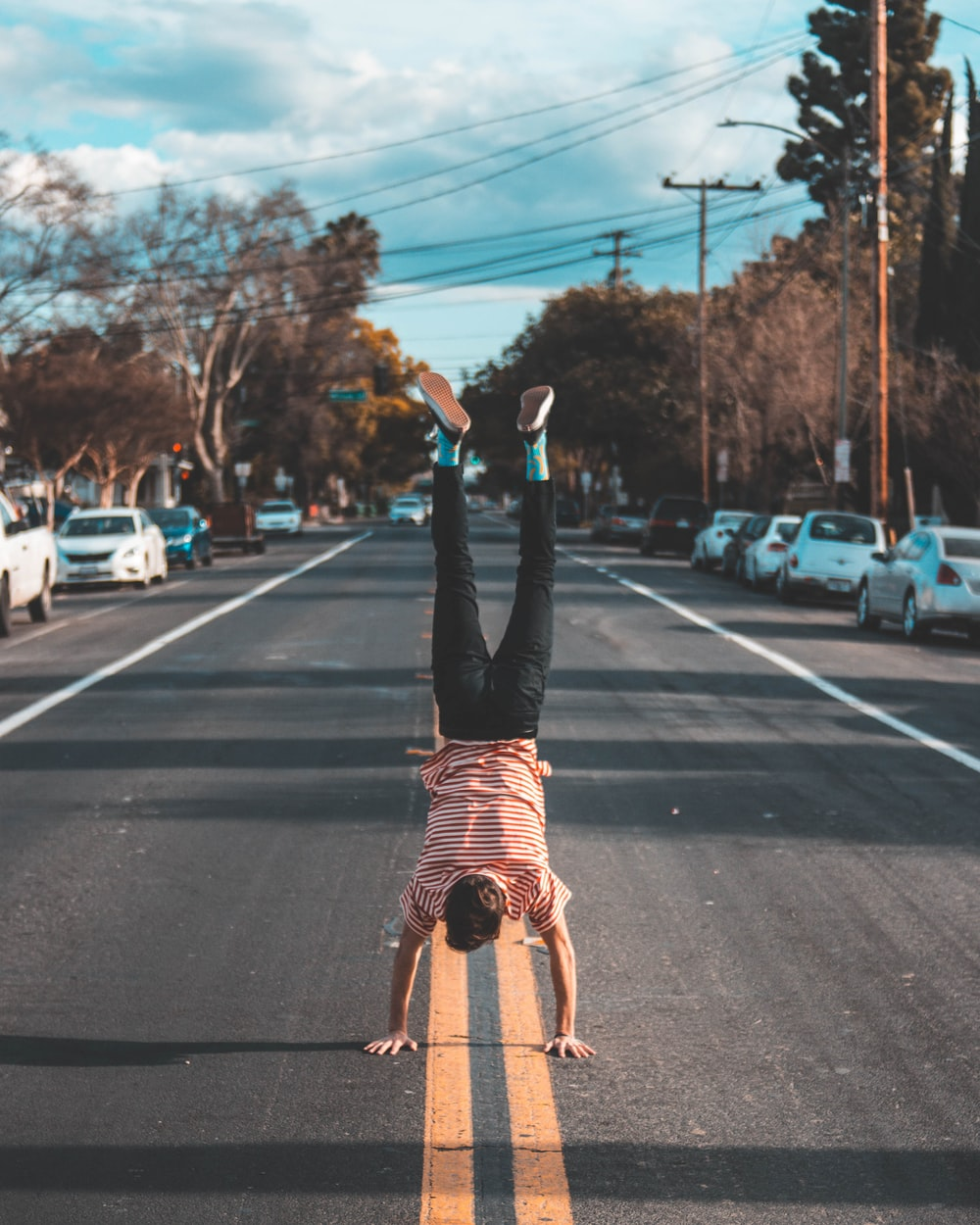 man doing hands stand on asphalt road between trees