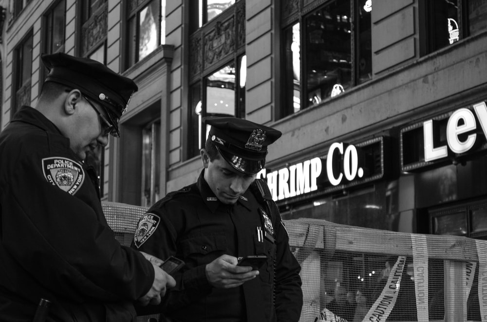 grayscale photo of two policemen standing near store