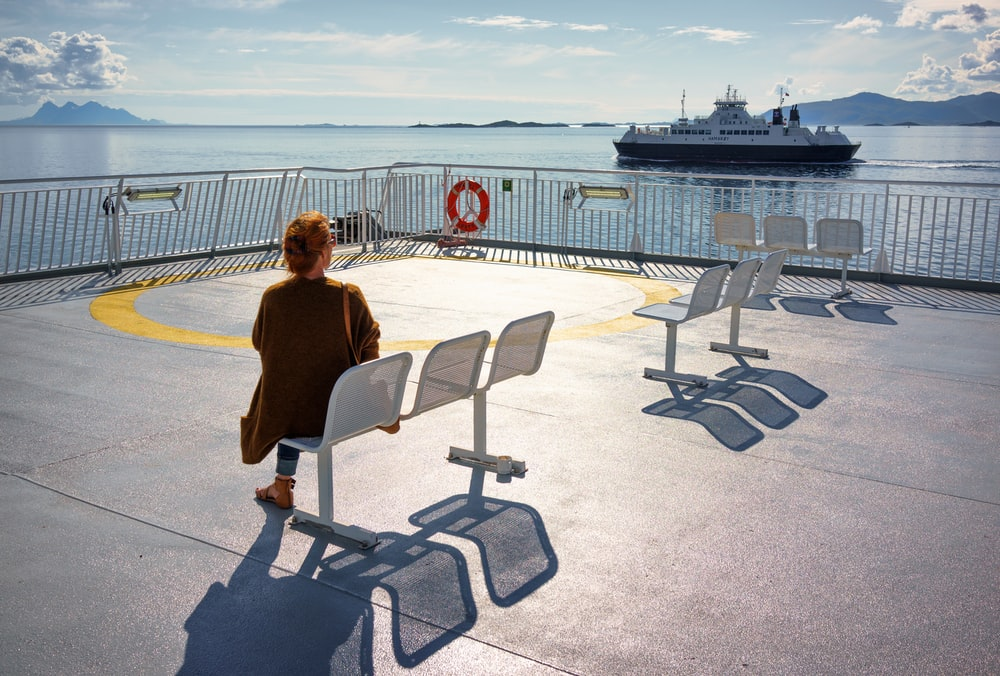 woman in brown cardigan sitting on white steel chair looking at the boat on the sea