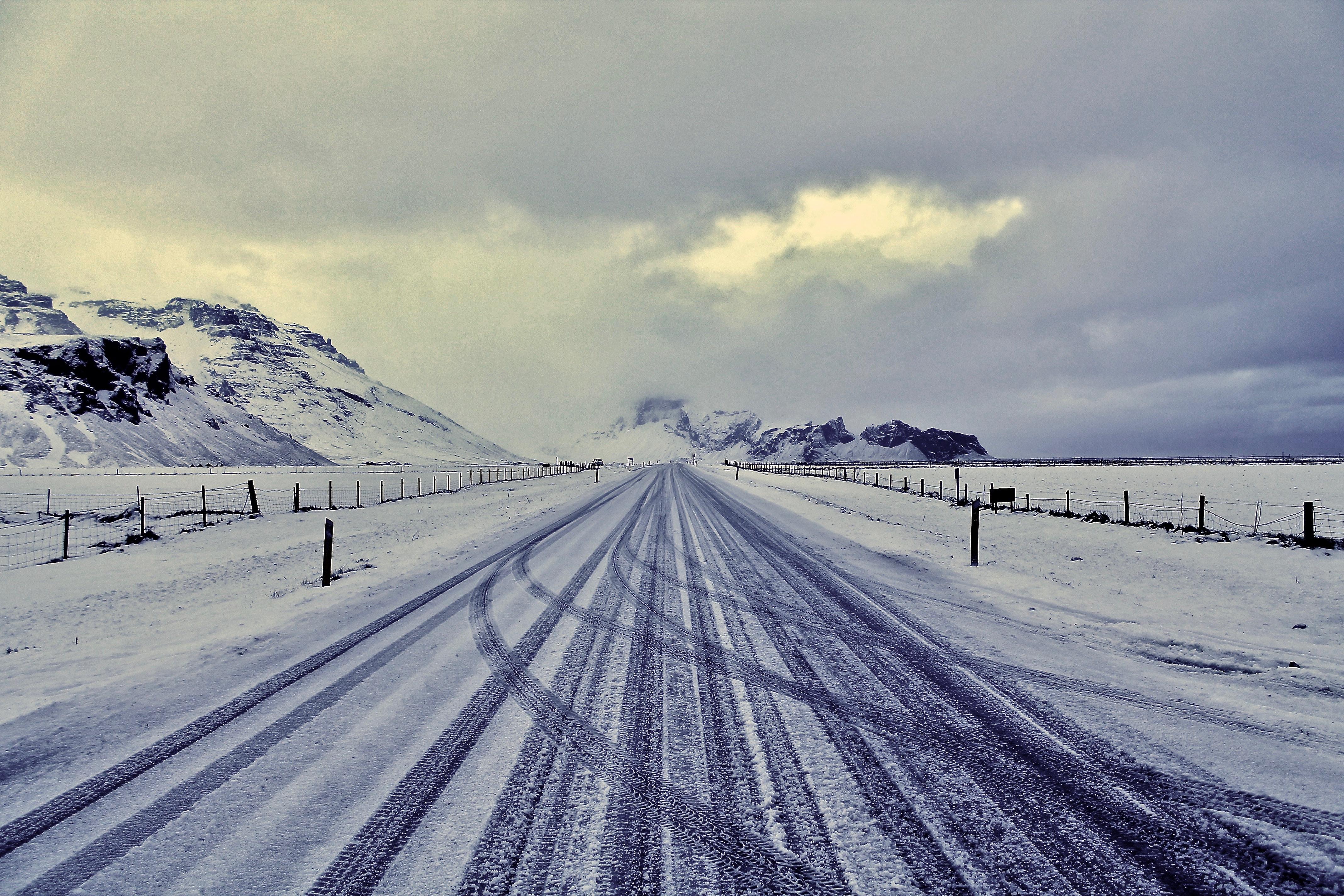 snow road with drift tire print near mountain range