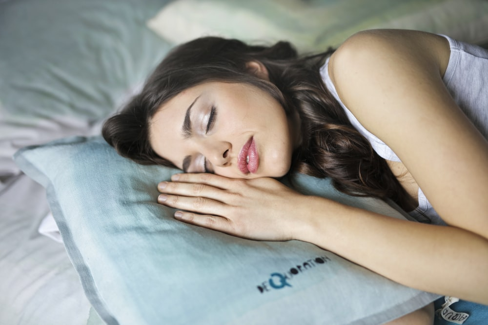 woman sleeping on blue throw pillow