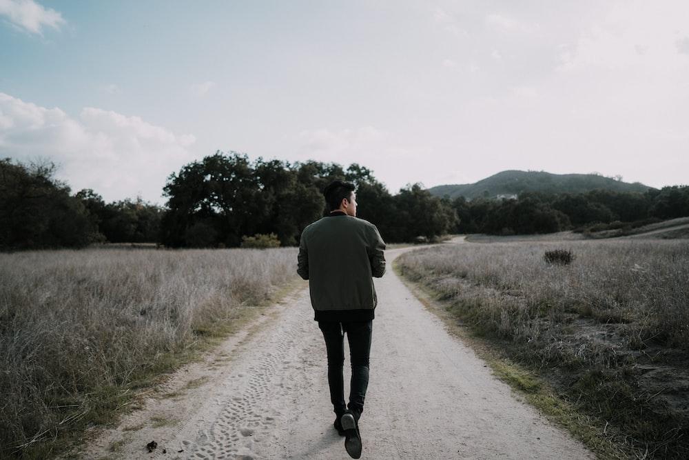 man walking on empty road