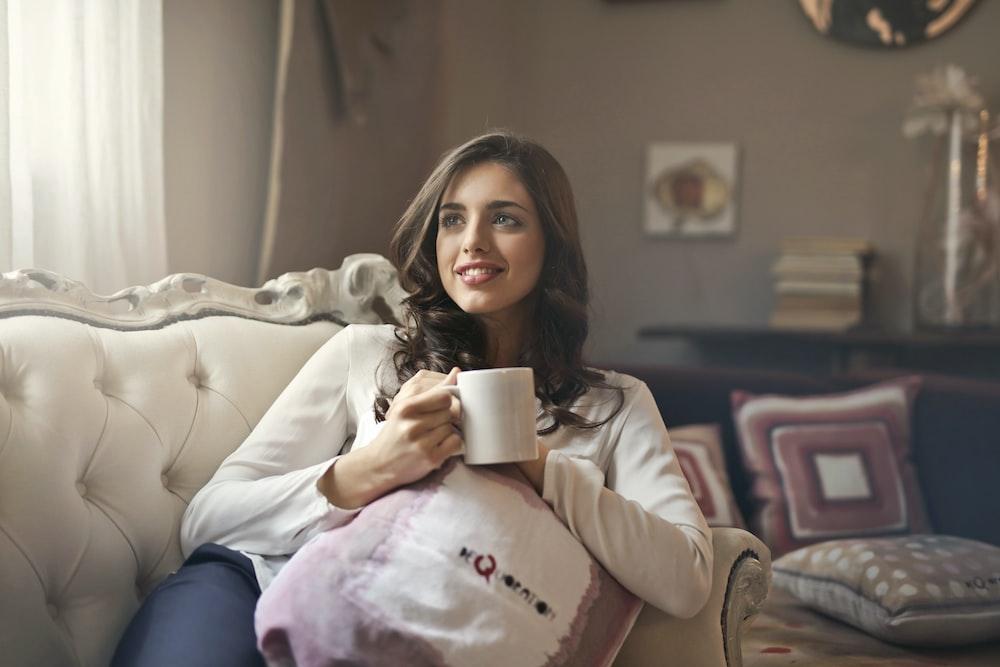 woman holding mug sitting on sofa