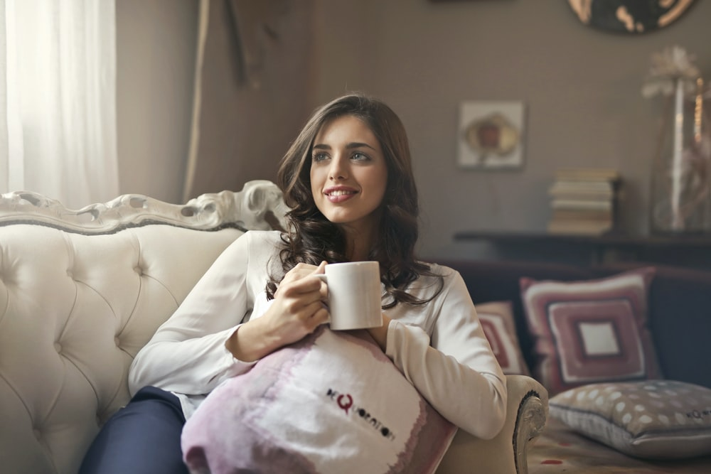 woman holding mug sitting on sofa