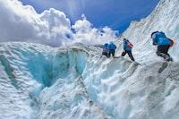 four people climbing mountain at daytime