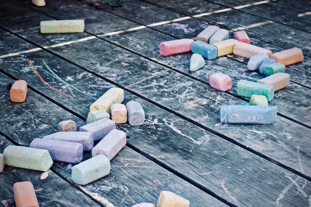 assorted-color color chalks on black wooden surface