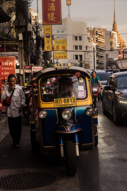man standing beside yellow auto rickshaw