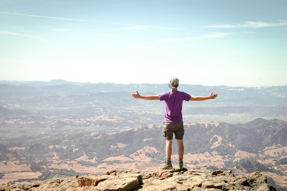 man stand on brown mountain under blue sky