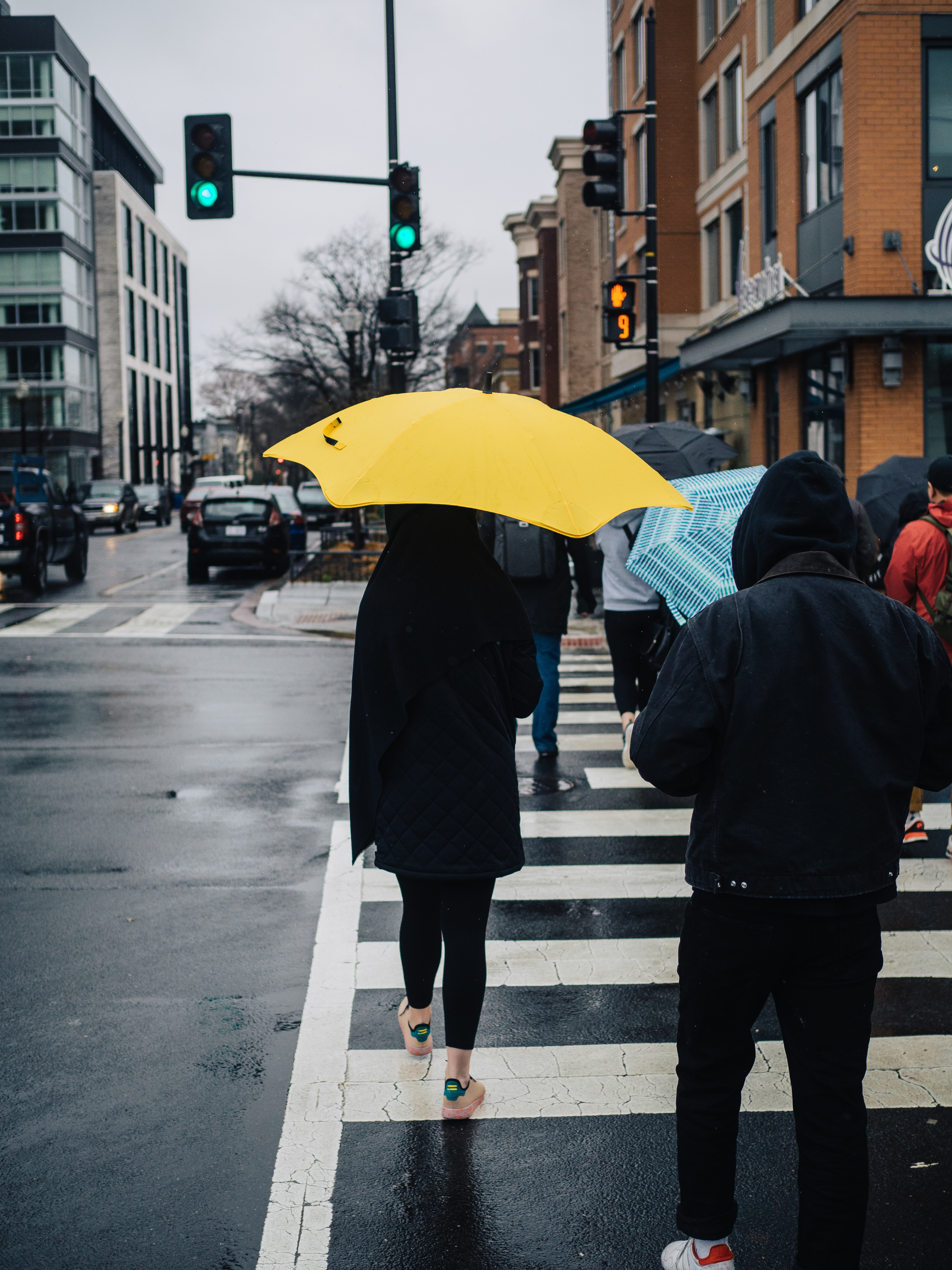 person holding yellow umbrella while crossing pedestrian