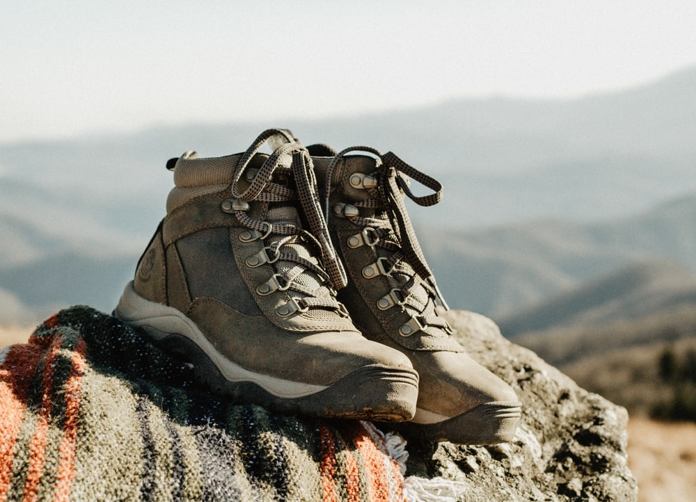 pair of brown high-top shoes on rock