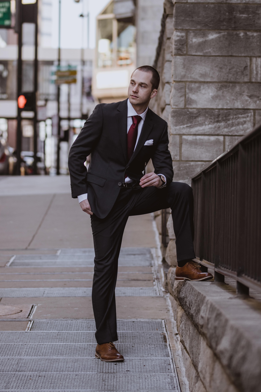 man in black formal suit standing beside concrete building