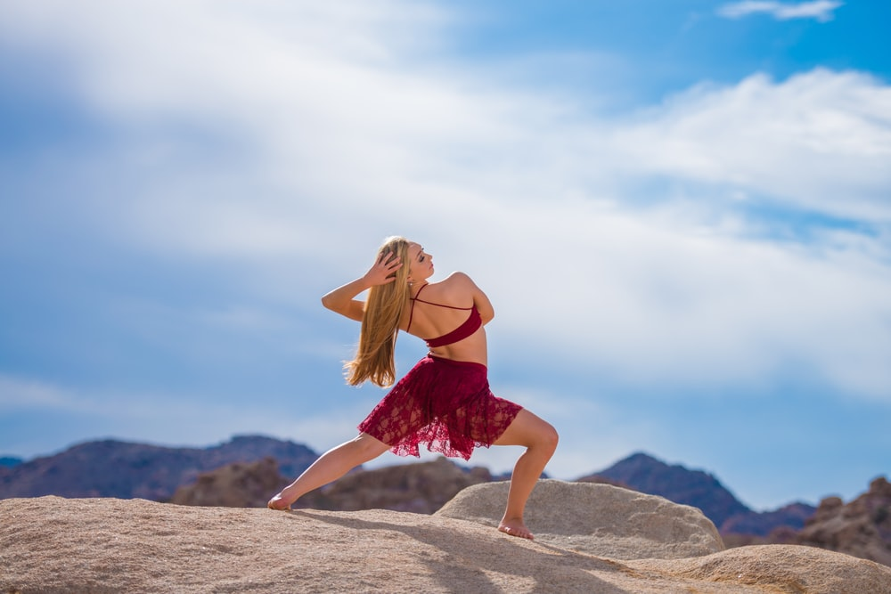 woman dancing near mountain under white clouds during daytime
