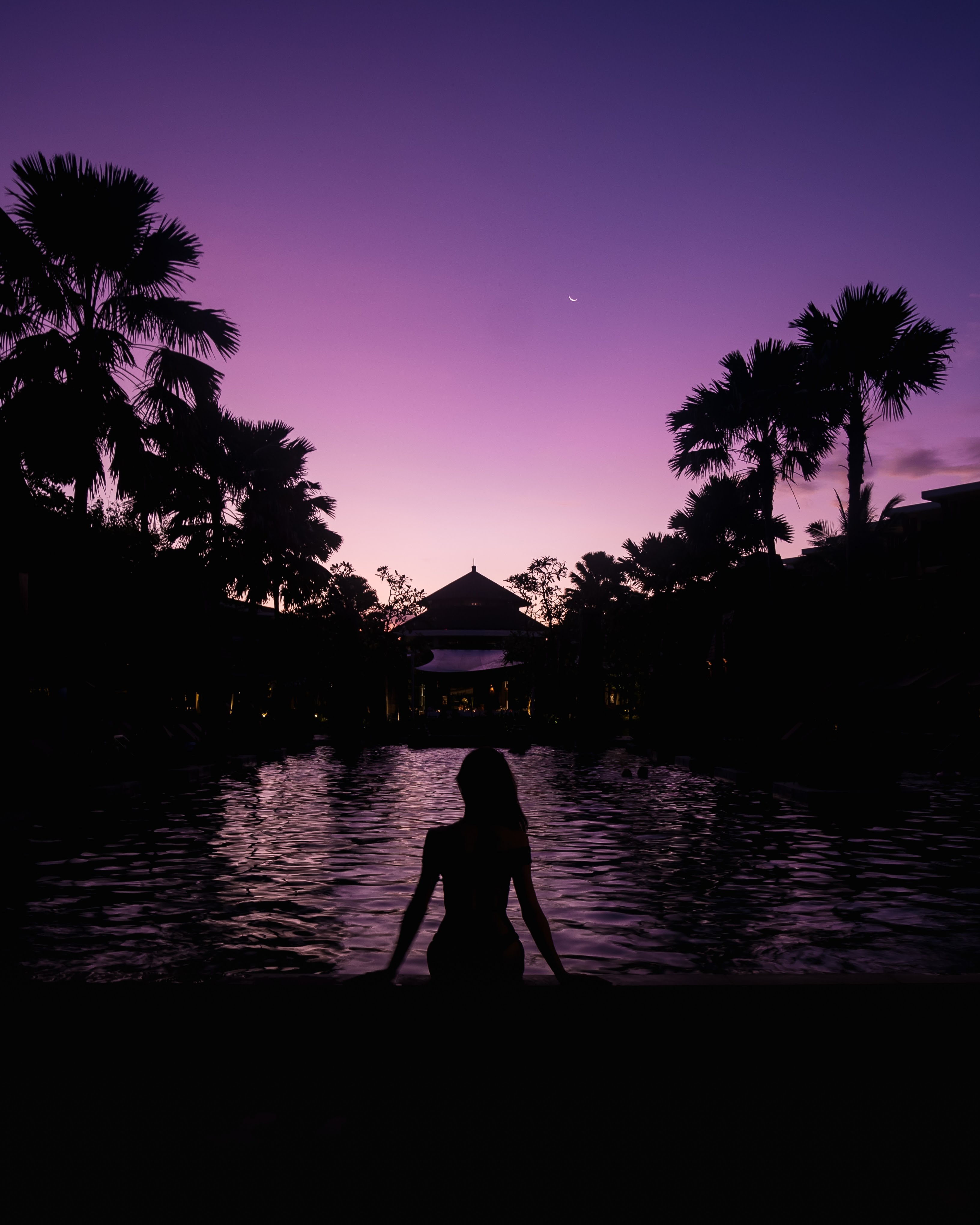 silhouette of woman sitting on edge of the pool during nighttime
