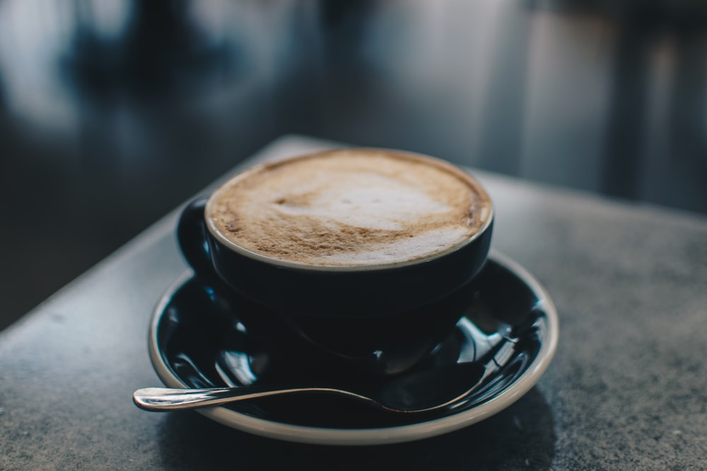 photo of black teacup filled with coffee on saucer