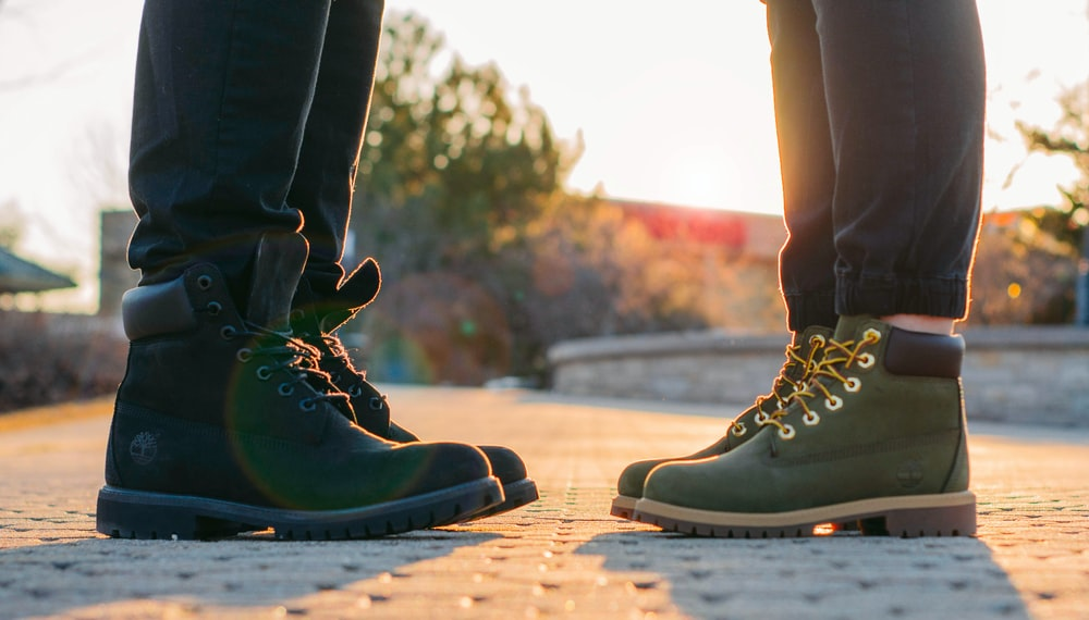 two people wearing green-and-black work boots standing on gray concrete pavement